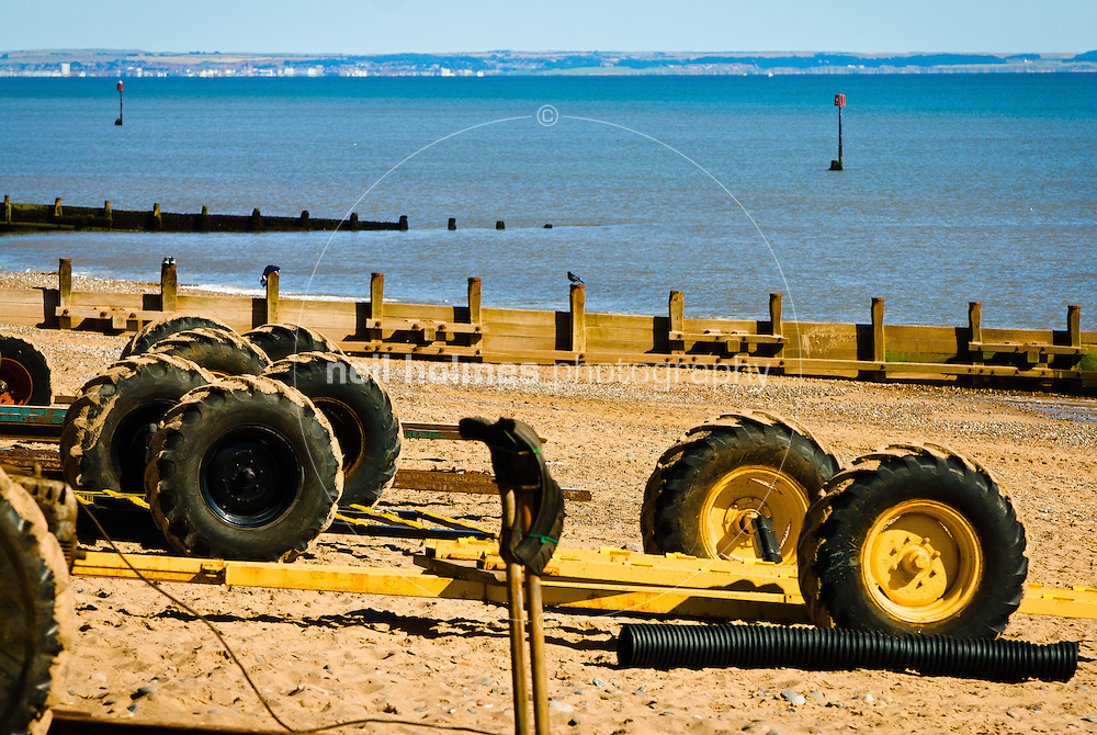 Yellow boat trailers waiting for the return of the fishing boats, summer 2007, Hornsea, East Yorkshire.