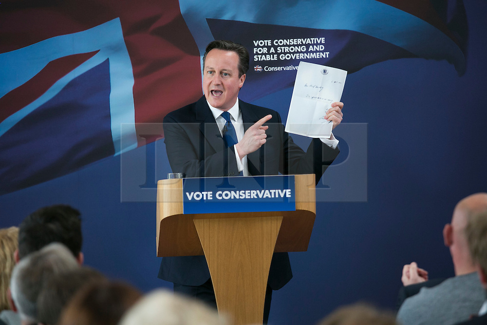 © Licensed to London News Pictures. 03/05/2015. Nuneaton, Warwickshire, UK. The Prime Minister David Cameron visited Ambleside sports club in Nuneaton, Warwickshire, earlier today. Pictured, David Cameron holds the letter left to him by the last Labour Government. Photo credit : Dave Warren/LNP