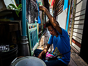 11 JULY 2017 - BANGKOK, THAILAND: A man baits a fishing line with crickets in a community built over the Chao Phraya River south of Krung Thon Bridge. The residents of the community expect to be evicted and their homes destroyed to make way for the city's plan to build a 14 kilometer long (22 mile) riverfront promenade. Thousands of families are expected to be evicted to accommodate the promenade. The riverside communities, built on stilts over the water, are prone to flooding and the city has been trying to control them for years. The houses are the only affordable housing for available to some of the poorest people in Bangkok.      PHOTO BY JACK KURTZ