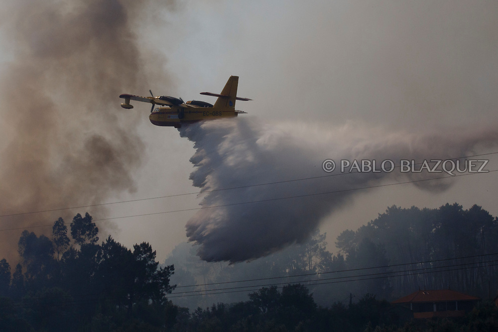 LEIRIA, PORTUGAL - JUNE 19:  A plane battles a fire from the air after a wildfire took dozens of lives on June 19, 2017 near Pedrogao Grande, in Leiria district, Portugal. On Saturday night, a forest fire became uncontrollable in the Leiria district, killing at least 62 people and leaving many injured. Some of the victims died inside their cars as they tried to flee the area.  (Photo by Pablo Blazquez Dominguez/Getty Images)