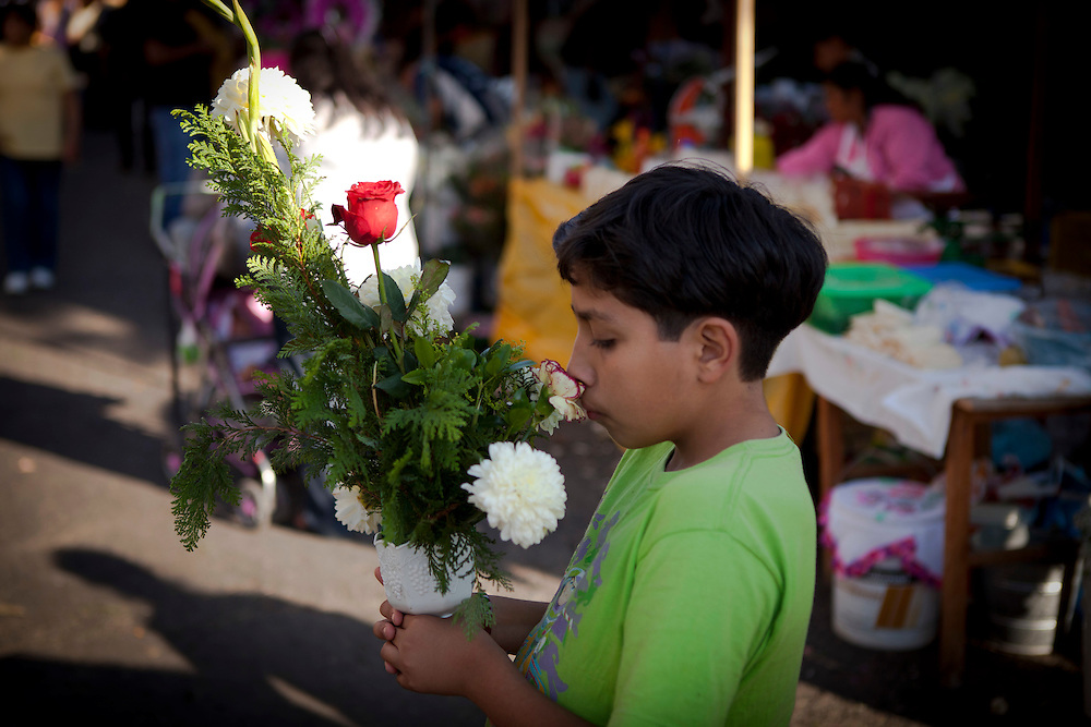 """A Mexican boy buys flowers in a street market in the town of Zacapu, Michoacan as an offering for a deceased family member to celebrate their life on """"Noche de Muertos"""" (Day of the Dead) on Nov. 2, 2011. ..©Benjamin B Morris"""