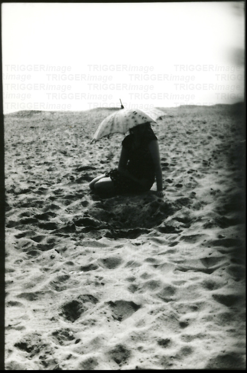 A young woman sitting on a sandy beach holding a sun shade
