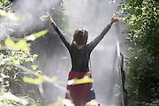 Happiness of a young woman in the woods and among the jets of water spray in Austria pavilion at Expo 2015, Rho-Pero, Milan, July 2015. In the pavilion was recreated a small forest where the temperature is 5 degrees Celsius lower than outside thereby eliminating the need for an air conditioning system. &copy; Carlo Cerchioli<br /> <br /> La felicit&agrave; di una giovane donna nel bosco e fra i getti d'acqua nebulizzata nel padiglione dell'Austria a Expo 2015, Rho-Pero, Milano, luglio 2015. Nel padiglione &egrave; stato ricreato un piccolo bosco dove la temperatura &egrave; di 5 gradi centigradi pi&ugrave; bassa di quella esterna eliminando cos&igrave; la necessit&agrave; di un impianto di condizionamento dell'aria.
