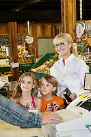 Happy woman with grandchildren standing by cash counter