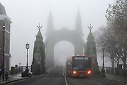 © Licensed to London News Pictures. 11/12/2013. London, UK. A bus crosses foggy Hammersmith Bridge.  Fog along the banks of the River Thames in Hammesmith, West London this morning 11th December 2013 . Photo credit : Stephen Simpson/LNP