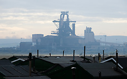 © Licensed to London News Pictures.20/10/15<br /> Redcar, UK. <br /> <br /> The recently closed SSI UK steel blast furnace forms a backdrop to the chimneys from the South Gare Fisherman's Association huts in Redcar, England. The closure of the site marks the end of 170 years of steel making heritage on Teesside and was the first of a number of recent closures of steel making plants across the UK.<br /> <br /> Photo credit : Ian Forsyth/LNP