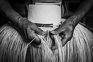 "2015/03/13 - Pile, Ecuador: Detail of Mariana Rivera, 73, hands weaving a ""Montecristi hat"" in her house early in the morning. She started to weave hats at the age of 10. Nowadays she doesn't weave the finest hats as before because her eyes are tired and old as she says. So, Mariana uses thicker straw to weave a hat, which brings the price down. She sells them at around US$200, but sometimes even less if she is really desperate for money.  UNESCO declared the ""Montecristi hat"" in 2012 as Intangible Cultural Heritage of Humanity."