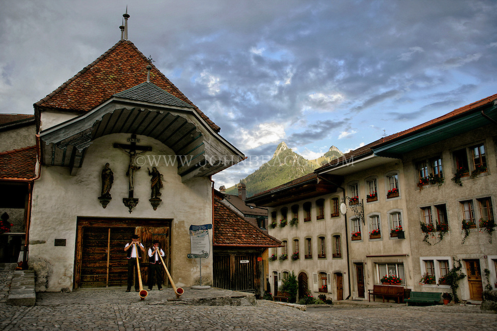 Men standing in front of a church playing Alphorns in the village, Gruyeres, Switzerland. Included is Mount Moléson, located in the Fribourg Alps.