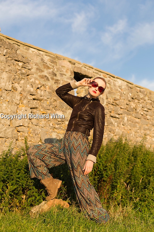 Woman in 1970's style clothing standing in front of a ruined building in the late evening sun.