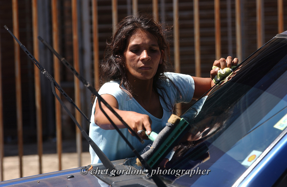 ASUNCION, PARAGUAY.  Paraguayan street mother cleans a windshield in Asuncion, Paraguay on Thursday evening, March 16, 2006. Hundreds of street children, some as young as 4 years old and their parents, work the diesel fumed streets of the capital city by squeegeeing windshields, panhandling and selling various items to drivers.