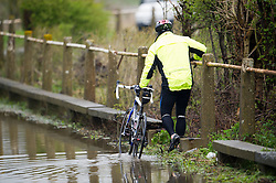 © London News Pictures. 29/04/2012. Margaretting, UK. A cyclist attempts to avoid getting wet in flood water on a road near the town of Margaretting in Essex on April 29, 2012 . The nearby river Wid broke it's banks following torrential rainfall. Photo credit : Ben Cawthra /LNP
