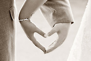 Sepia toned photo of a bride and groom creating a heart with their hands on their wedding day at Mallozzi's, Schenectady, NY