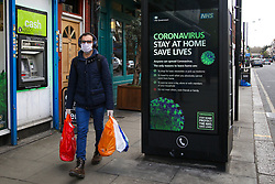 © Licensed to London News Pictures. 31/03/2020. London, UK. A shopper wearing a face mask walks past a 'Coronavirus Stay at Home Save Lives' public information poster in north London as lockdown continues. Photo credit: Dinendra Haria/LNP