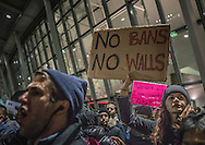 Protester holds a placard calling for no immigration bans and no border wall-building along the US-Mexican border at the Anti-Trump rally at John F. Kennedy International Airport, after the Trump administration implemented a ban on entry to citizens of 7 Muslim-majority nations into the United States.  New York, New York, USA.  28 January 2017