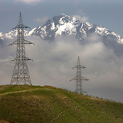Power lines carrying electricity from Uzbekistan to Kabul pass over the high mountains of the Hindu Kush and through lush valley's en route to the capital. Mazar to Kabul road, Afghanistan on the 12th of April 2009.
