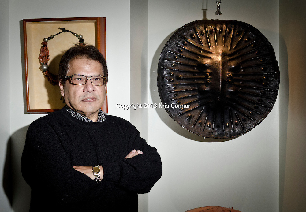 Mario Castillo of The Aegis Group poses for a portrait  in front of a 19th Century Ethiopian Buffalo Hide Shield at his home in northwest Washington D.C. on January 11, 2013. It was purchased because it is a shield and representative of the meaning behind the name of my firm, The Aegis Group, Ltd. Photo by Kris Connor