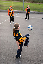 Teenage girls playing football UK