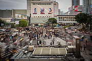 People cross the street either going to or coming from the well-known Hachiko exit of the Shibuya Railway Station
