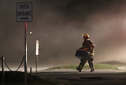 07 September 2010: A Brookline fire fighter is illuminated by the lights of a fire truck early in the morning. The call went out early Tuesday morning that a fire broke out at Atomic Fireworks, near the intersection of West Bypass and Sunshine. Credit: David Welker / TurfImages.com