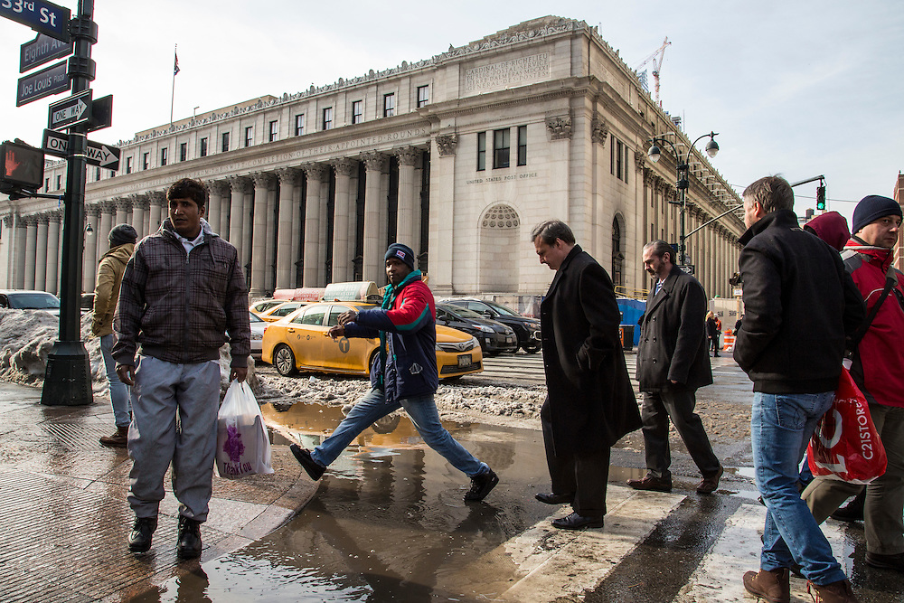 A black man steps over a large puddle opposite the United States Post Office, Eighth Avenue, New York City, New York, Unites States of America.  The puddle was caused by melting snow from the record breaking snowstorm January 2016.  Other pedestrians wait to walk past the water and there is traffic on the road behind.  (photo by Andrew Aitchison / In pictures via Getty Images)