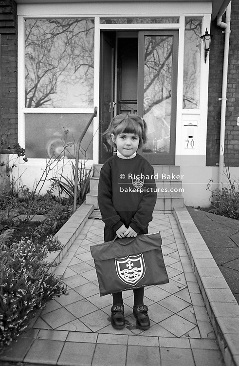A 5 year-old girl stands outside her south London home on the first day of proper school, a momentous day and a rite of passage.