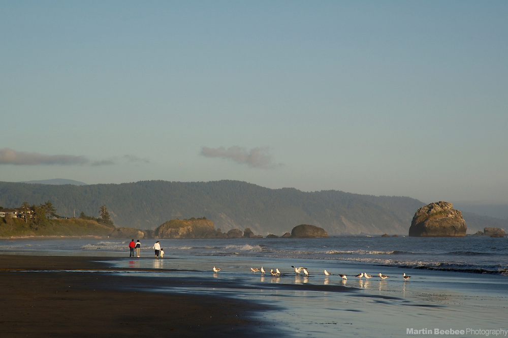 A family walks along the beach in Crescent City, California