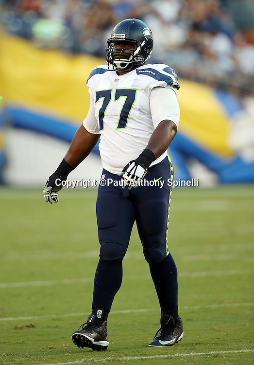 Seattle Seahawks nose tackle Ahtyba Rubin (77) looks on during the 2015 NFL preseason football game against the San Diego Chargers on Saturday, Aug. 29, 2015 in San Diego. The Seahawks won the game 16-15. (©Paul Anthony Spinelli)