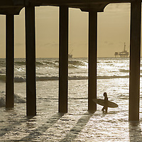 A surfer heads out just before sunset in Huntington Beach, CA.