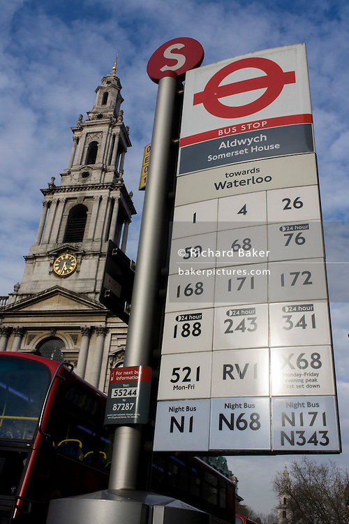 Beneath the church of St Mary le Strand, a bus stop at Aldwych, showing bus routes going south towards Waterloo and the Southbank in central London.