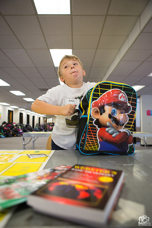 Aiden (7) volunteers with his mother, Shannon Hernandez, Symantec of Cupertino, at the Family Giving Tree in Milpitas, Calif., on Aug. 3, 2012.  Over 15,000 donated backpacks and school supplies will be processed during the Family Giving Tree's Back to School Drive.  Photo by Stan Olszewski/SOSKIphoto.