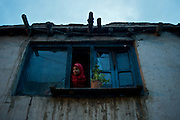 A young girl looks out of the window of her family home, Kargil
