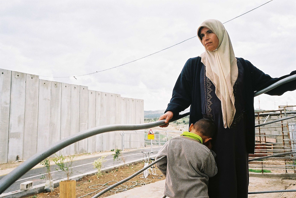 Between a rock and a hard place....Hani and his family are victims of circumstance. As the last home in the Palestinian village of Mescha, near Kalkila city, their house became the bordering property between Mescha and the Israeli settlement of Alkna, which sprung up next door. Two months ago, as the controversial ?security barrier? began to wind its way towards Mescha and Alkna, residents of Alkna complained that they did not want the wall built so close to the settlement. The result was a decision to bring the fence some 50 metres forward ? ultimately engulfing Hani?s property...Israel has defended the barrier as a necessary tool in fighting terrorism, but the building of the wall has its own victims. Locked between the settlement fence and the newly built security wall, Hani?s family property has been reduced to half a hectare of land surrounded in its entirety by concrete and wire fence ? an absurd no man?s land more akin to a zoo than a family home. ..Two months ago, it took Hani 15 minutes to walk to work and only a few minutes to visit his family living in the village. The route of the security fence has changed all of this. It takes Hani some two hours to make his way to work, and another two hours to return home, where his wife Mounira spends most of her day in dismal isolation. Entertaining is out of the question, as no one is allowed to cross the wall to visit the family. The couple must unlock an electronic gate to access their village or see their friends and family...In the garden, Gadad, their son, peers from behind the wire mesh fence at Israeli soldiers. A small remnant of the road cut off by the wall serves as a play area, where he rides his bike, but he does so alone...