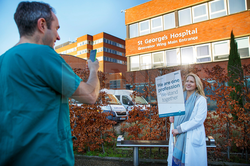 © Licensed to London News Pictures. 12/01/2016. London, UK. A doctor takes picture of a juniors doctor at a picket line outside St George's Hospital in Tooting, south London as junior doctors in England have gone on strike in a dispute with the government over a new contract on Tuesday, 12 January 2015. Photo credit: Tolga Akmen/LNP