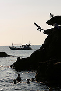 Phu Quoc Island. Duong Dong. Kids jumping into the sea from a rock.