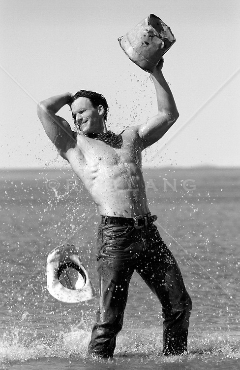 shirtless man enjoying splashing water on himself with a bucket of water in a lake