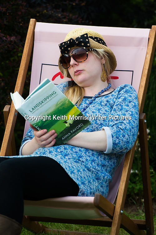 A young woman in a deckchair reading the book 'Landskipping' by Anna Pavord at the annual The Hay Festival of Literature and the Arts, 'the Woodstock of the Mind', Hay on Wye, Powys, Wales  UK May-June 2016<br /> <br /> Picture by Keith Morris/Writer Pictures