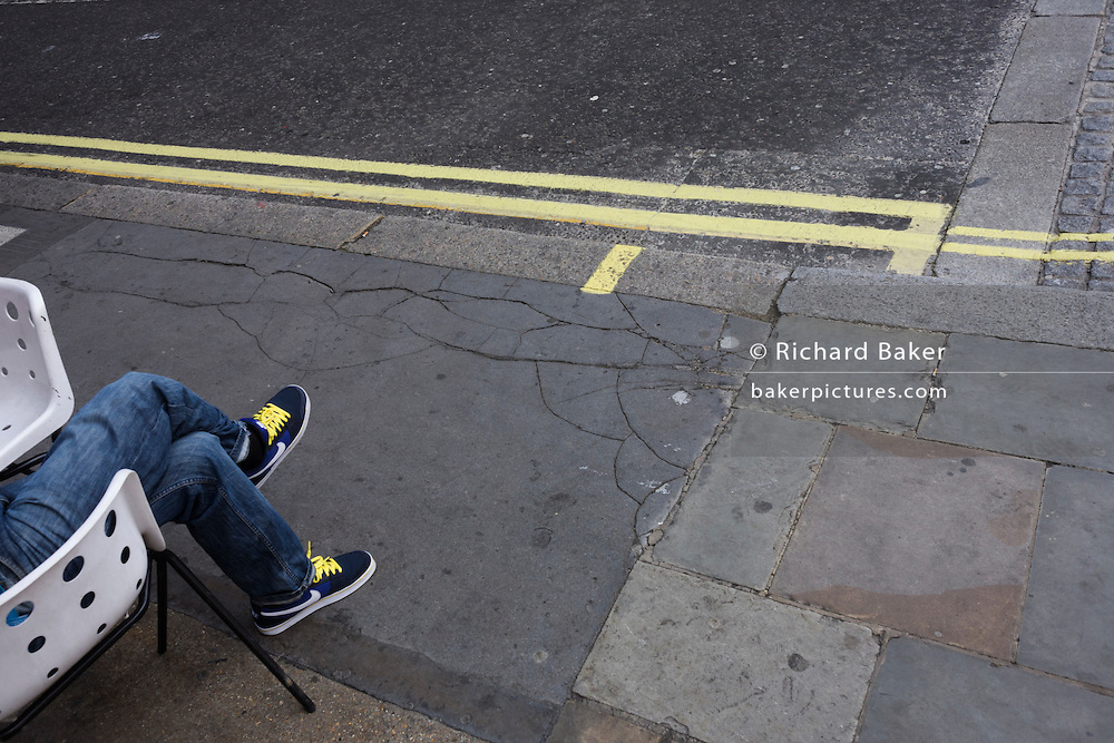 An anonymous person sits in a street, whose yellow shoe laces match nearby double-yellow no parking lines.