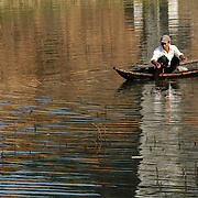 A fisherman casts his net from a wooden canoe in the shallow waters next to reeds in Hue, Vietnam.