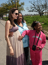 16 March 2008. New Orleans, Louisiana.<br /> A clearly pregnant Angelina Jolie poses with local residents in the Lower 9th Ward. She lets a young girl put her hands on her bump. She was in town for the 'Make it Right, Make a Commitment' with Brad Pitt. Make it Right Foundation aided by the Clinton Global Initiative.<br /> Photo by: Charlie Varley