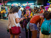 24 JULY 2018 - BANGKOK, THAILAND: A Thai woman sells curios to tourists on Khao San Road in Bangkok. Khao San Road is Bangkok's original backpacker district and is still a popular hub for travelers, with an active night market and many street food stalls. The Bangkok municipal government plans to shut down the street market by early August because city officials say the venders, who set up on sidewalks and public streets, pose a threat to public safety and could impede emergency vehicles. It's the latest in a series of night markets and street markets the city has closed.  PHOTO BY JACK KURTZ