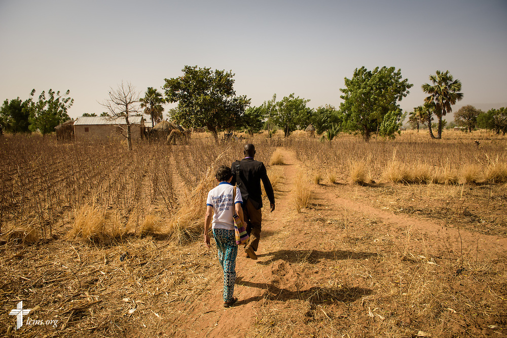 Valerie Stonebreaker, LCMS missionary to Togo, trails the Rev. Remi Lare Lambon, pastor in the Lutheran Church of Togo, as they walk to a home visitation on Tuesday, Feb. 14, 2017, at a rural village in Sankpong, Togo. LCMS Communications/Erik M. Lunsford