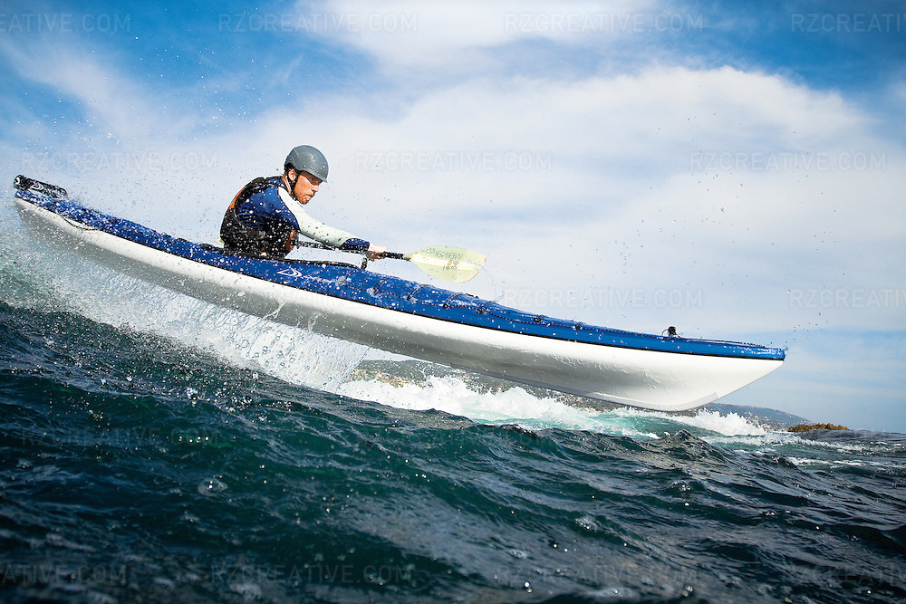 A sea kayaker launches his craft over a wave in Laguna Beach. Image is model released. Photo by Robert Zaleski/rzcreative.com
