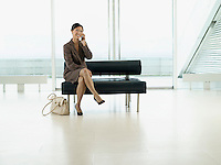 Businesswoman Sitting on Bench in airport talking on mobile