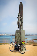 Recumbent in front of surf statue, Santa Cruz, Californai