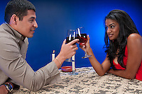 Latin couple drinking wine and toasting in a night club or restaurant setting.