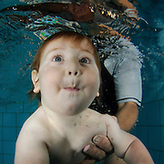 1 year old baby is supported underwater by his mother