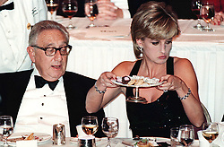 The Princess of Wales resists temptation and moves a plate of chocolates, despite a longing glance from Dr Henry Kissinger. The Princess was presented with the United Cerebral Palsy's Humanitarian Award at a dinner in the Hilton Hotel, New York.