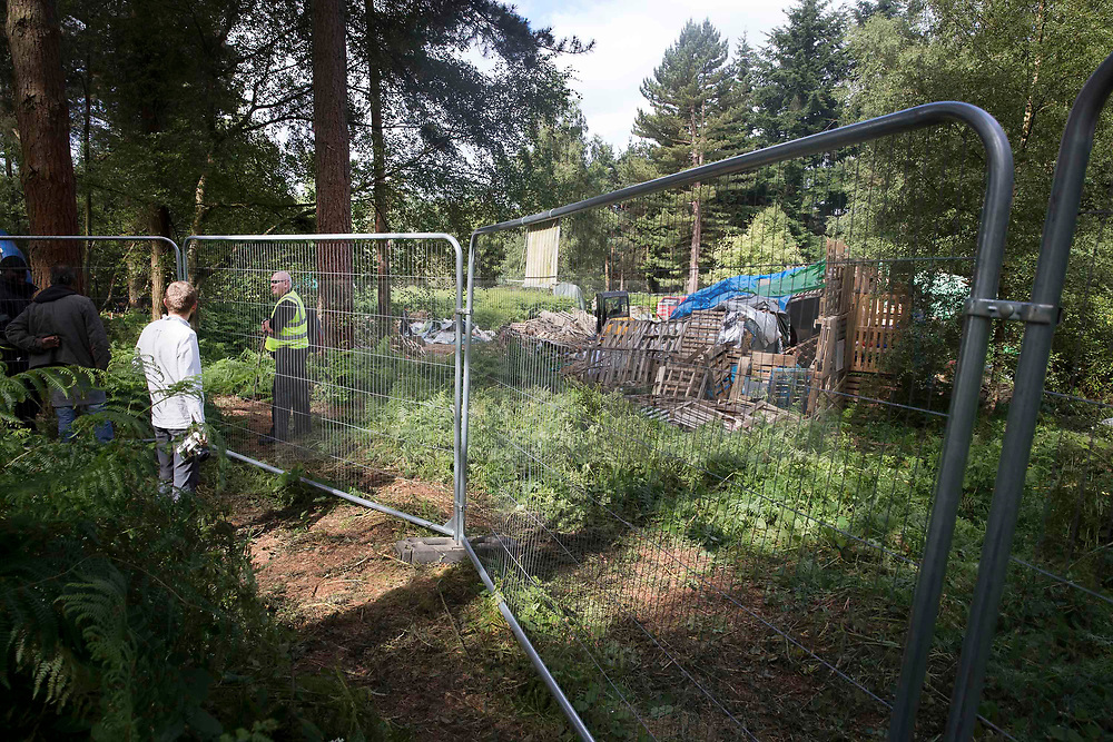 © Licensed to London News Pictures. 23/06/2017. Dorking, UK. A fence surrounds worker dismantling a protest fort built over an oil well site near Leith Hill in the North Downs . Protestors have been evicted from the camp over the last few days. Planning permission for 18 weeks of exploratory drilling was granted to Europa Oil and Gas in August 2015 after a four-year planning battle. The camp was set up by protestors in October 2016 in order to draw attention to plans to drill in this Area of Outstanding Natural Beauty (AONB) in the Surrey Hills. The camp has received support from the local community. Photo credit: Peter Macdiarmid/LNP