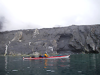 A kayak paddler close to a cliff at Spitzbergen