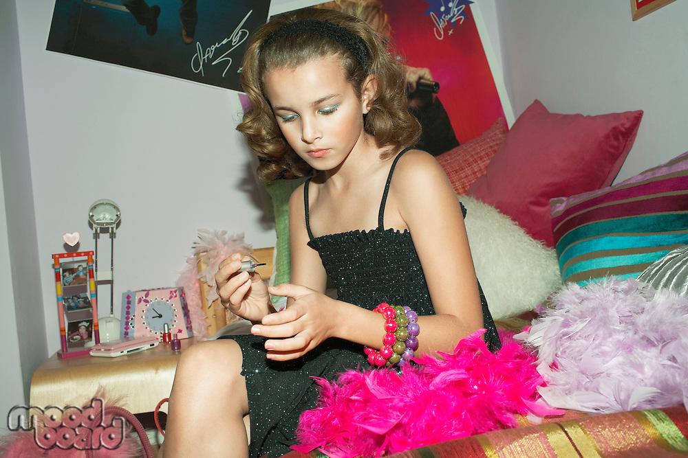Fashionable Young Girl Applying Nail Polish in trendy bedroom
